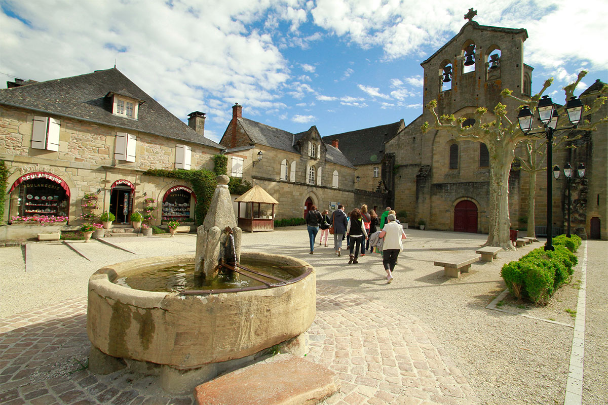 The central place of the village of Aubazine with a view on the abbey in Dordogne Valley in France