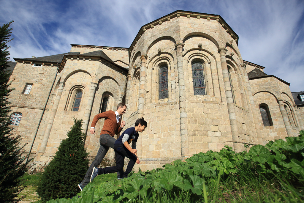A young boy and a man running in front of a church in Saint-Robert in the Dordogne Valley in the South West of France