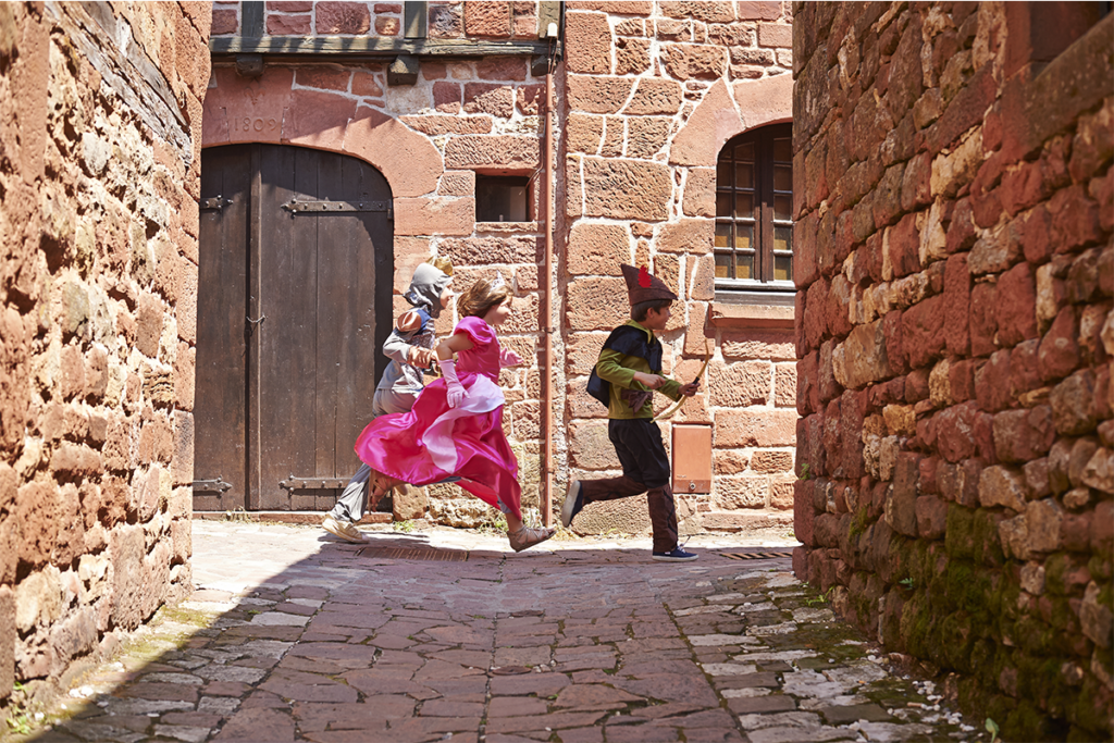 Three children playing in a medieval street in the Dordogne Valley in the South West of France